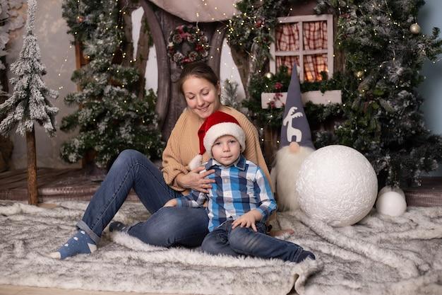 Jongen en moeder dichtbij kerstboom thuis