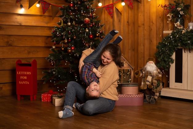 Jongen en moeder spelen in de buurt van de kerstboom