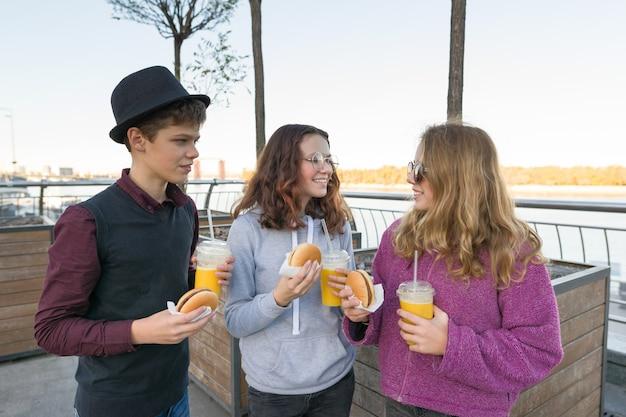 Jongen en twee meisjes op stadsstraat met burgers en jus d'orange