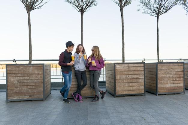 Jongen en twee meisjes op straat met hamburgers en jus d'orange