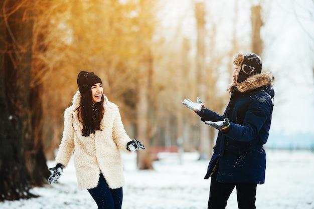 Jongen en vrouw spelen met sneeuw in met sneeuw bedekte park