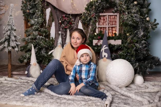 Jongen en zijn moeder dichtbij kerstboom, stuk speelgoed huis en kabouters.