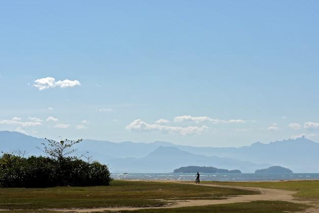 Jongen fietsen op het strand, met heuvels en heldere hemel