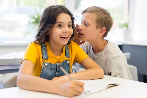 Jongen fluistert tegen meisje in de klas