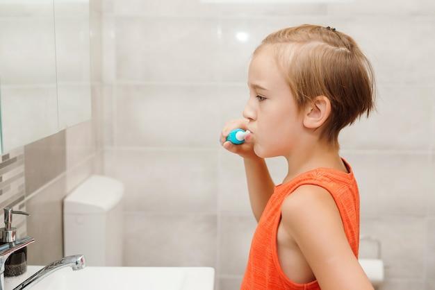 Jongen geeft om de gezondheid van zijn tanden. gelukkige jongen die tanden schoonmaakt. kid tandenpoetsen met elektrische borstel in de badkamer. elke dag mondhygiëne. gezondheidszorg, kindertijd en mondhygiëne.