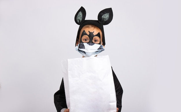 Jongen gekleed als een vleermuis met een witte snoepzak met lege ruimte. het virus heeft de wereld aangevallen.