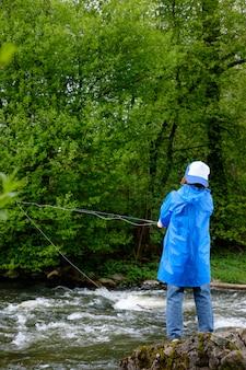 Jongen, gekleed in blauwe waterdichte regenjas en pet, vissen op de berg stromende rivier. uitzicht vanaf de achterkant