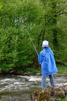 Jongen, gekleed in blauwe waterdichte regenjas en pet, vissen op de berg stromende rivier