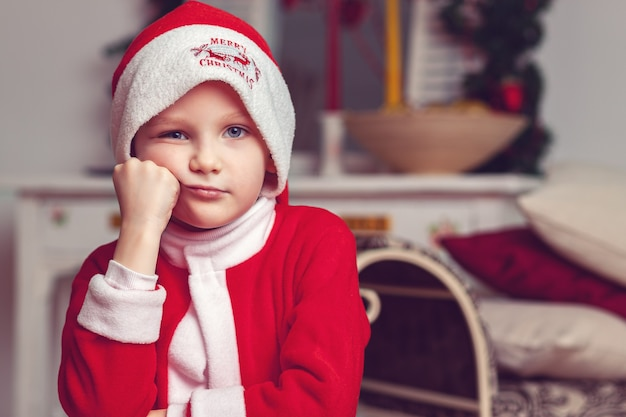 Jongen gekleed in een rood pak als de kerstman in een mooie kamer
