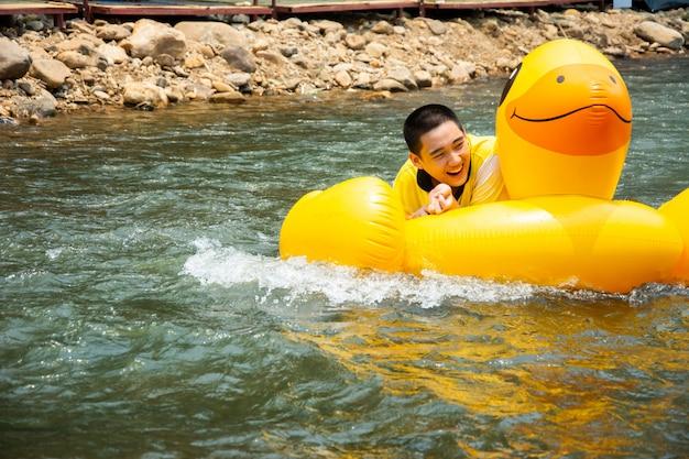 Jongen geniet van en heeft plezier roeiend stroomafwaarts op kanaal