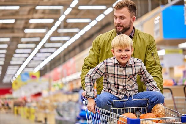 Jongen geniet van winkelen tijd met vader in de supermarkt, knappe jongen zoon op een kar dragen, veel plezier