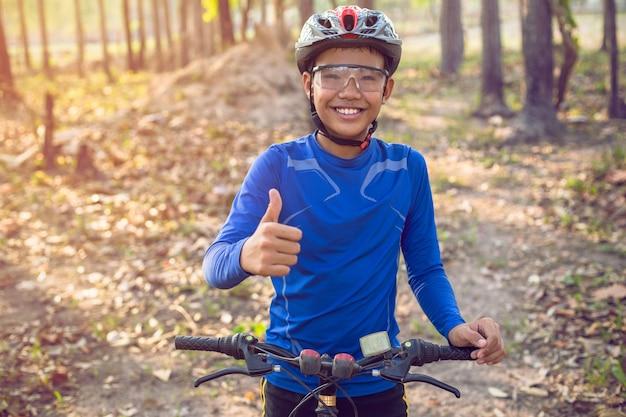 Jongen genoot van de fiets in het bos.