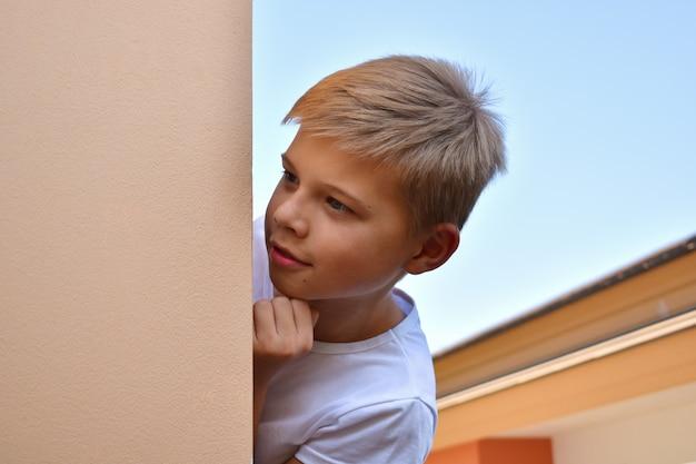 Jongen gluurt om de hoek van het huis
