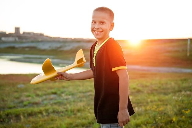 Jongen gooit een speelgoedvliegtuigje in de zomer bij zonsondergang een kind speelt met een speelgoedvliegtuigje droomt van een reis...