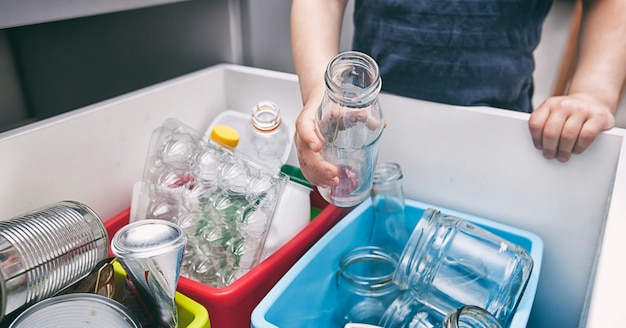 Jongen gooit het afval naar een van de vier verschillende bakken voor het sorteren van afval