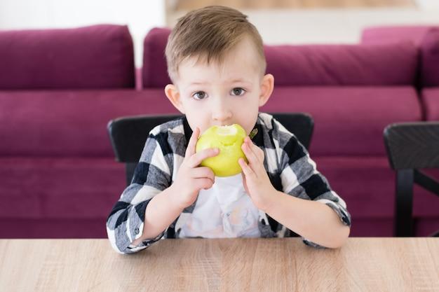 Jongen groene appel eten aan de tafel in de woonkamer.