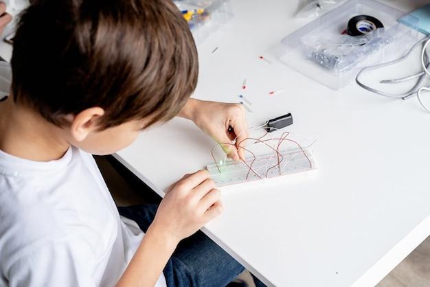 Jongen handen werken met led-verlichting op experimenteel bord voor wetenschappelijk project
