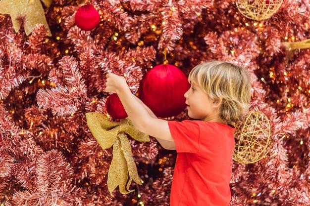 Jongen hangt een versiering aan de rode kerstboom