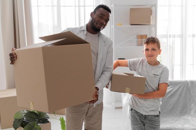Jongen helpt zijn vader om pakjes te dragen om te verhuizen