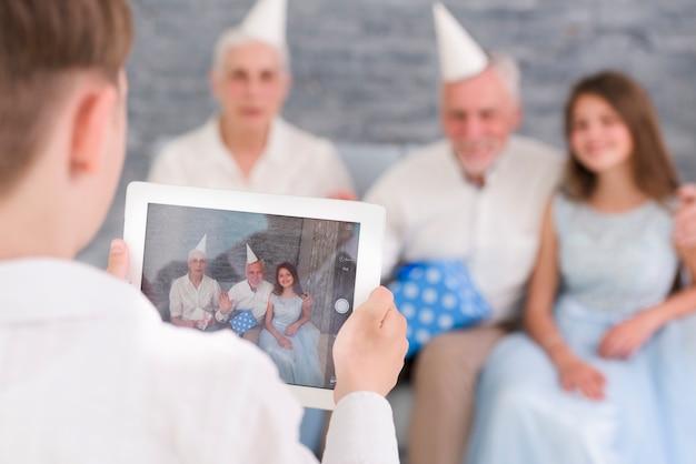 Jongen het klikken familiefoto door digitale tablet thuis