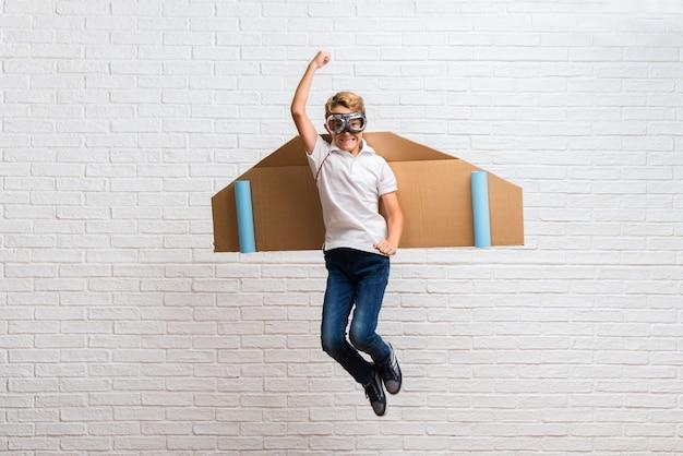 Jongen het spelen met de vleugels van het kartonvliegtuig het springen