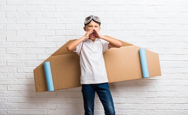 Jongen het spelen met de vleugels van het kartonvliegtuig op zijn rug die met wijd open mond schreeuwen