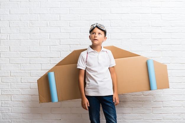 Jongen het spelen met de vleugels van het kartonvliegtuig op zijn rug die twijfels hebben en met verward gezichtsuitdrukking