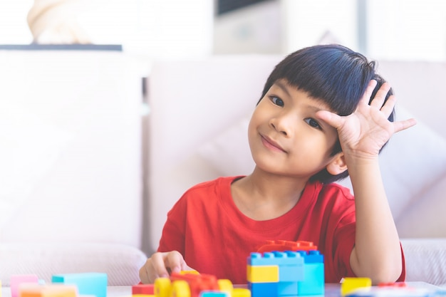 Jongen het spelen stuk speelgoed de blokken in woonkamer met hand zeggen hallo omhoog