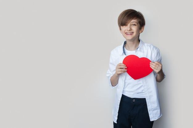 Jongen houdt een hart van papier glimlachen