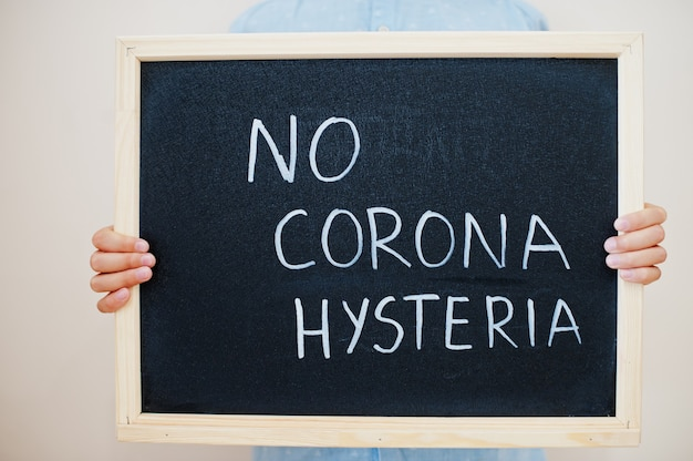 Jongen houdt inscriptie op het bord met de tekst geen corona hysterie