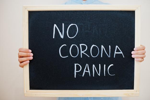 Jongen houdt inscriptie op het bord met de tekst geen corona paniek