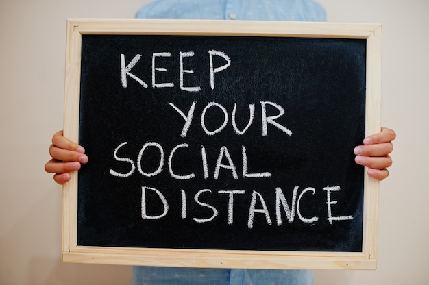 Jongen houdt inscriptie op het bord met de tekst houd je sociale afstand