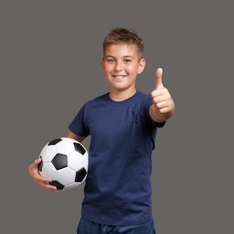 Jongen houdt voetbal en gebaren duimen omhoog