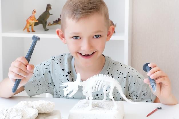 Jongen houdt zich bezig met de opgraving van dinosaurussen. educatief spel met kinderen. een kind graaft de botten van een dinosaurus op. ontwikkeling van doorzettingsvermogen en fijne motoriek. gelukkige jongen