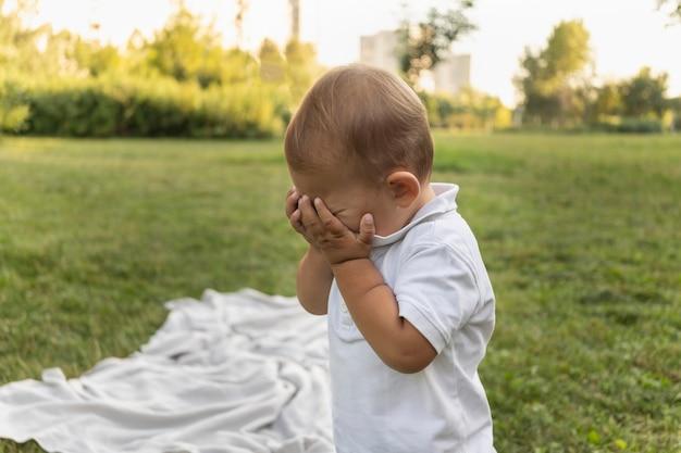 Jongen huilt op straat peuter schreeuwt buiten kind is stout in park moeilijk leeftijdskind met