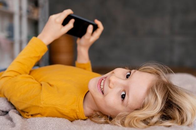 Jongen in bed spelen op mobiel