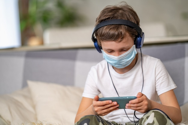 Jongen in beschermend masker en koptelefoon, met smartphone in zijn handen.