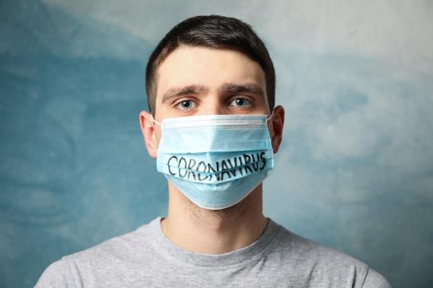 Jongen in beschermend masker met inscriptie coronavirus op blauw.