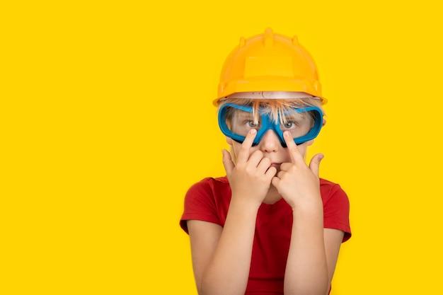 Jongen in beschermende helm en veiligheidsbril op gele muur