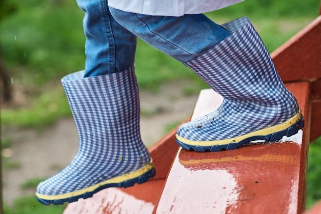 Jongen in blauwe rubberen laarzen de natte gladde trappen in regenachtige dag. kind veiligheidsconcept