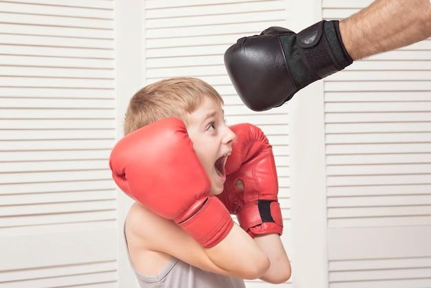 Jongen in bokshandschoenen gevechten met een man hand in een handschoen.