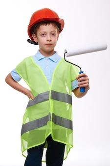 Jongen in bouw groen vest en oranje helm holding paint roller op witte geïsoleerde achtergrond