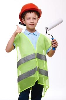 Jongen in bouw groen vest holding paint roller toont duim omhoog gebaar op witte geïsoleerde achtergrond