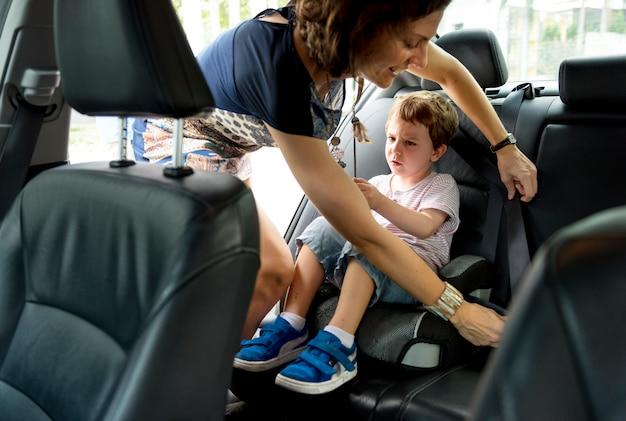 Jongen in de auto met behulp van autostoel beveiliging te beschermen