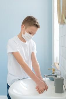 Jongen in de badkamer die zijn handen wast
