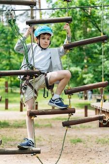 Jongen in de beschermende helm stapt voorzichtig op de touwladder. jongen in een opvouwbaar park