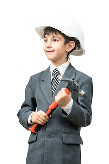 Jongen in de bouwhelm en het jasje met een hamer