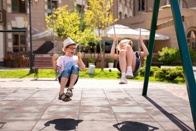 Jongen in de bril en hoed en blondemeisje in de kleding die pret op een schommeling samen in mooie de zomertuin hebben.