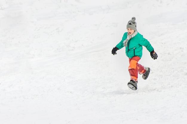 Jongen in de groene jas en rode broek loopt door de sneeuw.