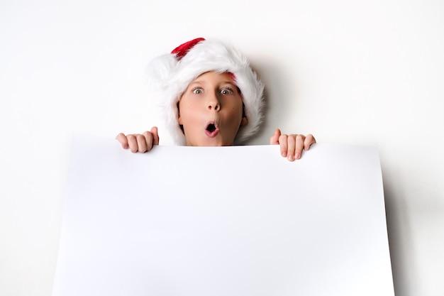 Jongen in de hoed van de kerstman verrast en houdt wit leeg bord voor groeten. geïsoleerd op wit